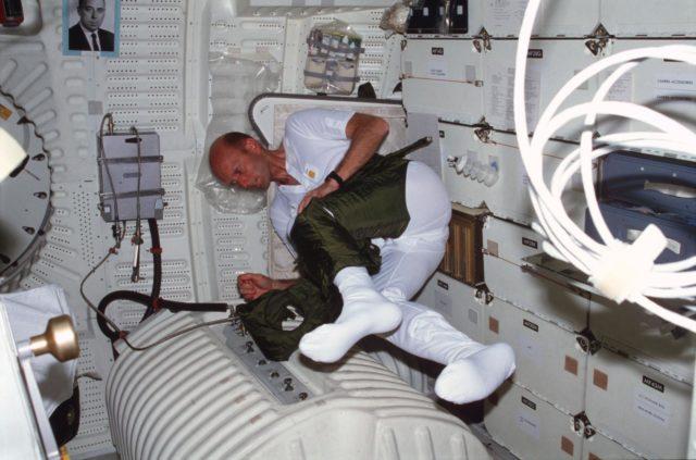 Pilot Fullerton dons EES anti-gravity suit lower torso on middeck