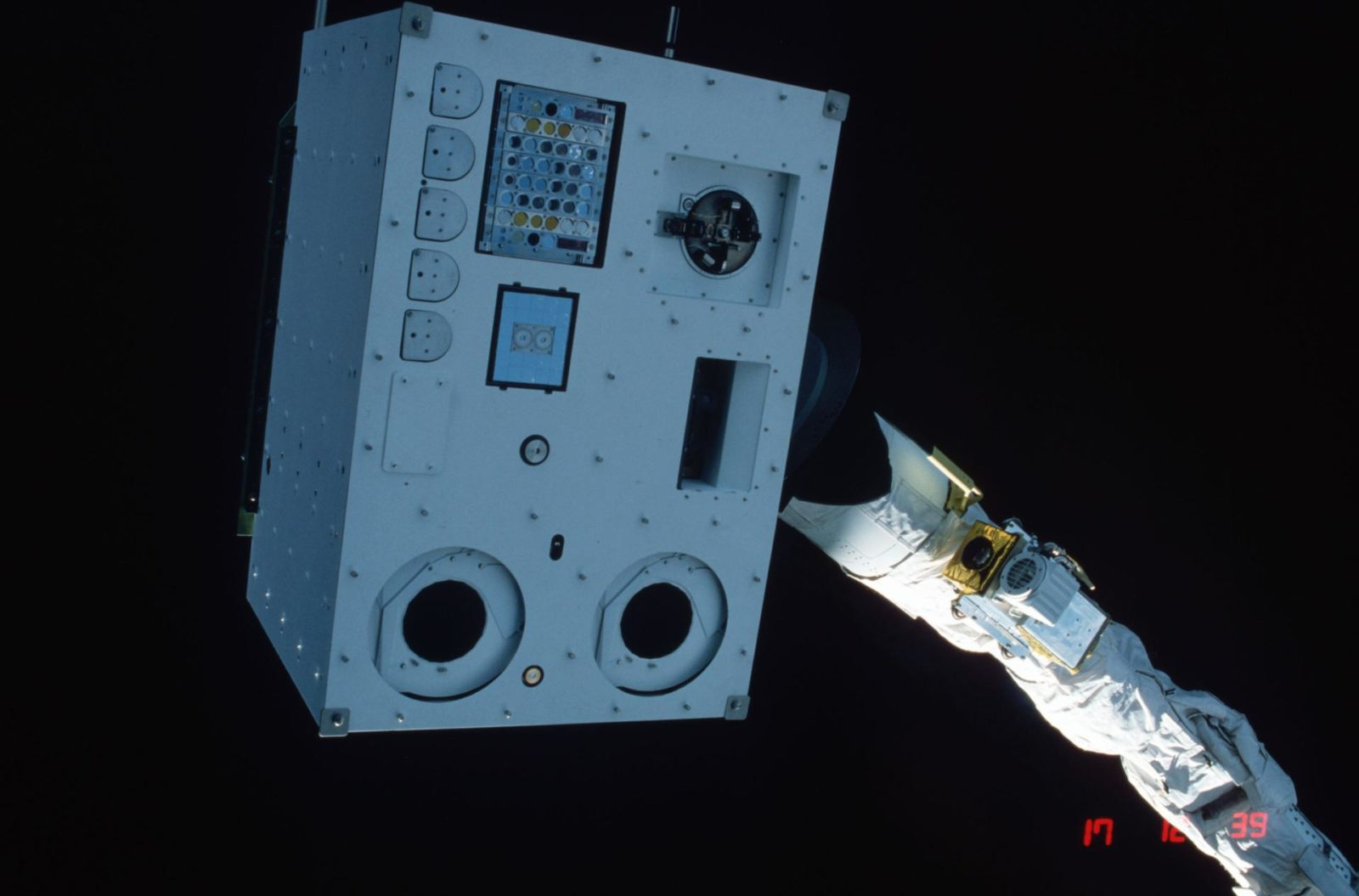 Closeups of IECM grappled by RMS and positioned above payload bay (PLB)