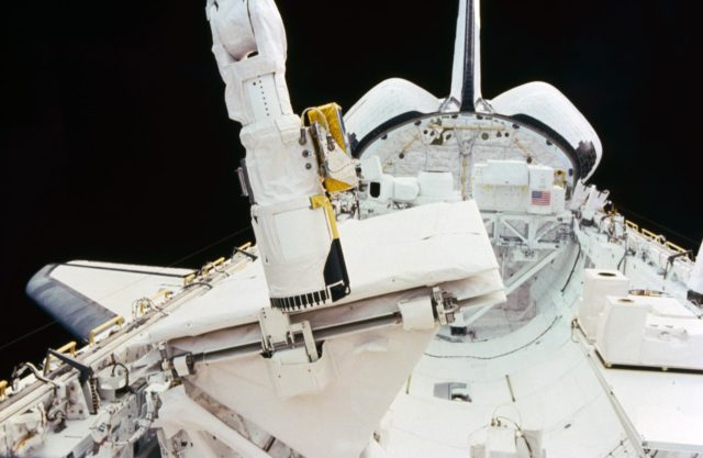 View of the RMS end effector touching the SIR-B antenna during STS 41-G