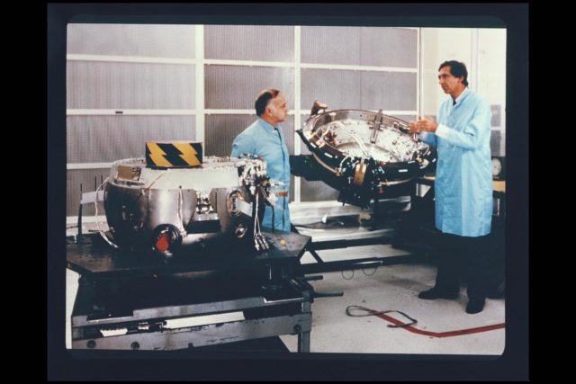 Photo by JPL Pioneer Galileo Probe Orbiter being tested at JPL  (being inspected  byAngelo 'Gus' Gustaferro and John Vojvodich) ARC-1985-AC85-0354-6