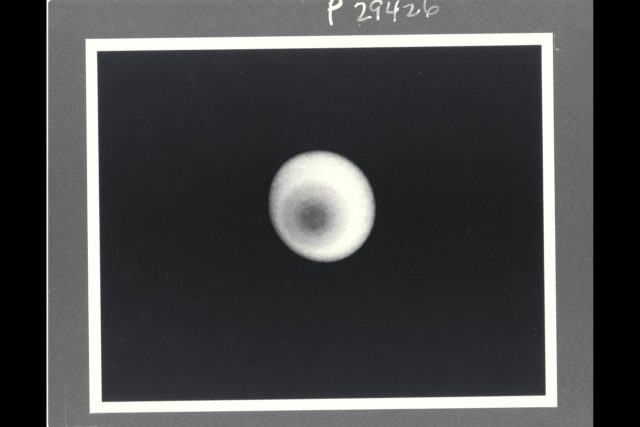 Range :  36 million km. ( 22 million miles ) P-29426B/W This Voyager 2 photograph of Uranus shows the is the  first picture to show clear evidence of latitudinal banding in the planet's atmosphere.  This is a computerized summation of five images shot by the narrow angle camera. The concentric pattern emanates like a bulls-eye from the planets pole of rotation, which, in this view, lies left of center. uranus lies almost on its side with respect to the other planets  and is rotating in a counter clockwise direction, as seen here. Clouds in the Uranian atmosphere give rise to the pattern, the first clear evidence of banding similiar to that seen previosly on Saturn and Jupiter. The bandind on Uranus, however, shows much less contrast. At the distance at which the images were acquired, Voyager's camera could have detected individual features as small as 660 km. (410 miles) across, but no such cloud or markings  were apparent. Scientists cannot yet say what properties, such as cloud height, composition, or particle size, are giving rise to the varying levels of brightness visible here. The images composing this picture  were shot through a filter that transmits only violet light. in the original, unprocessed images, the contrast of features  producing the banding is low, not more than 10 percent. In order to reduce 'noise' and enhance the visiblity of the features, processors  combined five images  and then compared the resulting  composite to a hypothetical featureless planet illuminated  by the Sun from  the proper direction. Only the ratio between the original data and the hypothetical image is shown. ARC-1985-A86-7002