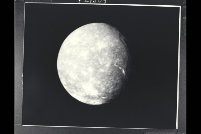 P-29509 BW Range: 500,000 kilometers (300,000 miles) This high-resolution image of Titania was made as Voyager 2 neared its closest approach to Uranus. Voyager's narrow-angle camera acquired this image  through the violet and clear filters and shows details about 9 km (6 mi) in size. Titania has a diameter of about 1,600 km (1,000 MI). In addition to many scars due to impacts, Titania displays evidence of other geologic activity at some point in its history. The large trench-like feature near the terminator (day-night boundary) at middle right suggests at least one episode of tectonic activity, Another, basinlike structure near the upper right is evidence of an ancient period of heavy impact activity. The neutral gray color of Titania is characteristic of the Uranian satellites as a whole. ARC-1986-A86-7025