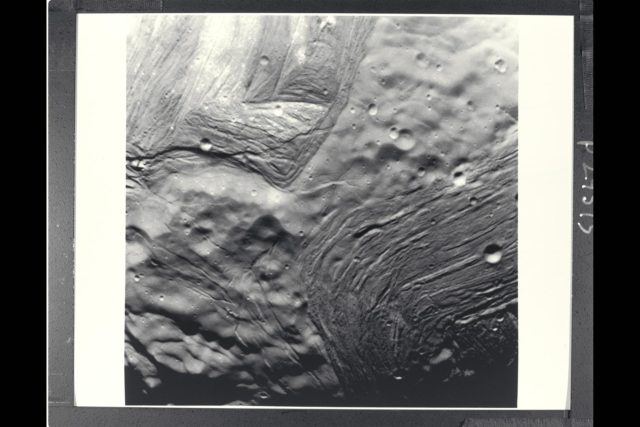P-29515 BW Range: 42,000 kilometers (26,000 miles) This image of Miranda, obtained by Voyager 2 on approach, shows an unusual 'chevron' figure and regions of distinctly differing terrain on the Uranian moon. Grooved areas baring light and dark bands, distinct from other areas of mottled terrain, are visible at this resolution of about 600 meters (2,000 feet). The bright V-shaped feature in the grooved areas is the 'cheron' observed in earlier, lower-resolution images. Cutting across the bands are sinuous scarps, probably faults. Superimposed on both types of terrain are many bowl-shaped impact craters less than 5 km (3 mi) wide. The entire picture spans an area about 220 km (140 mi) across. ARC-1986-A86-7031