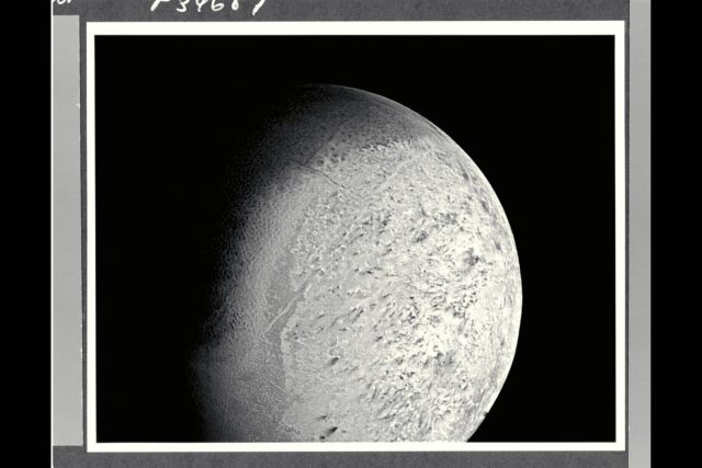 P-34687 Range :  530,000 km. ( 330,000 miles ) Smallest Resolvable Feature :  10 km or 6 miles This Voyager 2 image of Neptune's satellite Triton shows the first photo of Triton to reveal surface topography. The south pole, continuously illuminated by sunlight at this season, ia at bottom left. the boundary between bright southern hemisphere and the darker and the darker, northern hemisphere is clearly visible. Both the darker regions to the north and the very bright sub-equatorial band show a complex pattern of irregular topography that somewhat resembles 'fretted terrain' on parts of Venus and Mars. The pattern of dark and light regions over most of the southern hemisphere will require higher resolution images for interpretation. Also evident are long, straight lines that appear to be surface expressions of internal, tectonic processes. No large impact ctaters are visible, suggesting that the crust of Triton has been renewed relatively recently, that is, within the last bllion years or less. ARC-1989-A89-7025