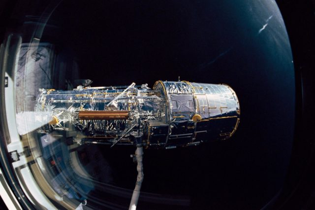 Hubble Space Telescope (HST) grappled by OV-103's RMS during STS-31 checkout