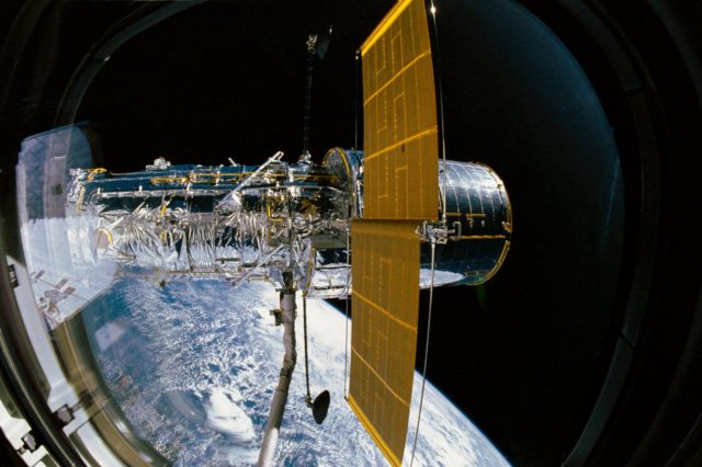 STS-31 Hubble Space Telescope (HST) (SAs & HGAs deployed) is grappled by RMS