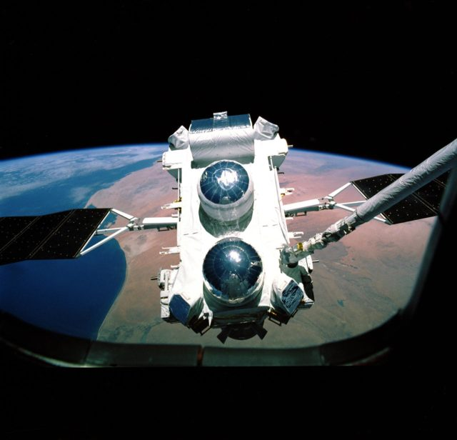 This photograph shows the Compton Gamma-Ray Observatory (GRO) being deployed by the Remote Manipulator System (RMS) arm aboard the Space Shuttle Atlantis during the STS-37 mission in April 1991. The GRO reentered Earth atmosphere and ended its successful mission in June 2000. For nearly 9 years, the GRO Burst and Transient Source Experiment (BATSE), designed and built by the Marshall Space Flight Center (MSFC), kept an unblinking watch on the universe to alert scientists to the invisible, mysterious gamma-ray bursts that had puzzled them for decades. By studying gamma-rays from objects like black holes, pulsars, quasars, neutron stars, and other exotic objects, scientists could discover clues to the birth, evolution, and death of stars, galaxies, and the universe. The gamma-ray instrument was one of four major science instruments aboard the Compton. It consisted of eight detectors, or modules, located at each corner of the rectangular satellite to simultaneously scan the entire universe for bursts of gamma-rays ranging in duration from fractions of a second to minutes. In January 1999, the instrument, via the Internet, cued a computer-controlled telescope at Las Alamos National Laboratory in Los Alamos, New Mexico, within 20 seconds of registering a burst. With this capability, the gamma-ray experiment came to serve as a gamma-ray burst alert for the Hubble Space Telescope, the Chandra X-Ray Observatory, and major gound-based observatories around the world. Thirty-seven universities, observatories, and NASA centers in 19 states, and 11 more institutions in Europe and Russia, participated in the BATSE science program. n/a