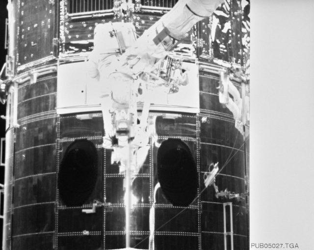 Astronaut Jeffrey Hoffman on RMS robot arm during HST repairs