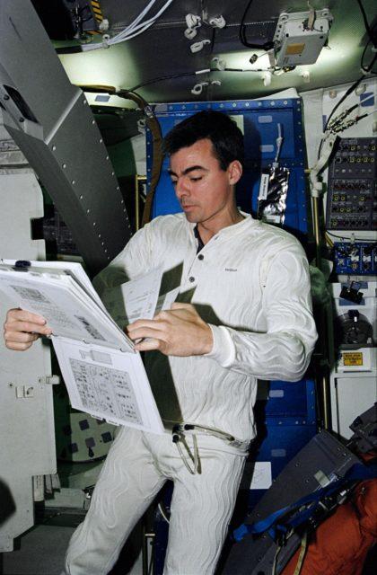 Astronaut Andrew Allen looks over procedure book in middeck