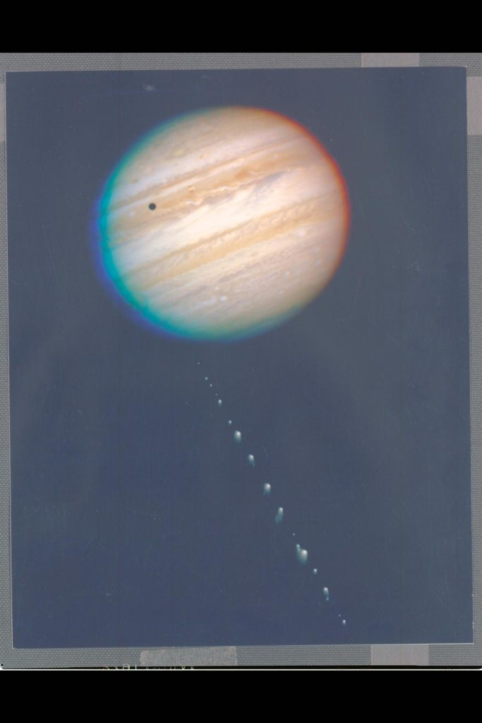 This is a composite photo, assembled from separate images of Jupiter and Comet P/Shoemaker-Levy 9 as imaged by the Wide Field & Planetary Camera-2 (WFPC-2), aboard NASA's Hubble Space Telescope (HST).  Jupiter was imaged on May 18, 1994, when the giant planet was at a distance of 420 million miles (670 million KM) from Earth. This 'true-color' picture was assembled from separate HST exposures in red, blue, and green light. Jupiter's rotation between exposures creates the blue and red fringe on either side of the disk. HST can resolve details in Jpiter's magnifient cloud belts and zones as small as 200 miles (320 km) across (wide field mode). This detailed view is only surpassed by images from spacecraft that have traveled to Jupiter.   The dark spot on the disk of Jupiter is the shadow of the inner moon Io. This volcanic moon appears as an orange and yellow disk just to the upper right of the shadow. Though Io is approximately the size of Earth's Moon (but 2,000 times farther away), HST can resolve surface details.  When the comet was observed on May 17, its train of 21 icy fragments stretched across 710 thousand miles (1.1 million km) of space, or 3 times the distance between Earth and the Moon. This required six WFPC exposures along the comet train to include all the nuclei. The image was taken in red light.  The apparent angular size of Jupiter relative to the comet, and its angular separation from the comet when the images were taken, have been modified for illustration purposes.  CREDIT: H.A. Weaver, T.E. Smith (Space Telescope Science Institute (STSI)) and J.T. Tranuger, R.W. Evans (Jet Propulsion Laboratory (JPL)) and NASA. (HST ref: STSci-PR94-26a) ARC-1994-AC94-0353-1