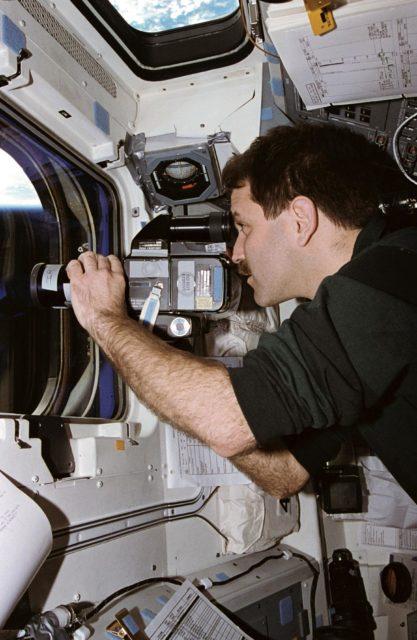 Astronaut John Grunsfeld uses camera to record ASTRO-2 payload