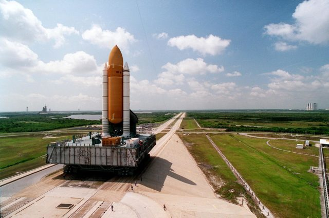 The Space Shuttle Discovery slowly and carefully makes the 4.2- mile (6.8 kilometer) trek from the Vehicle Assembly Building, background at right, to Launch Pad 39B on its Mobile Launcher Platform carried by the Crawler Transporter. Pad 39A, with the Shapce Shuttle Atlantic poised for liftoff, is in background at left. Discovery is scheduled to fly first, on STS-70 targeted for June 8. Atlantis' mission, STS-71, is scheduled no earlier than June 22. KSC-95PC-0669
