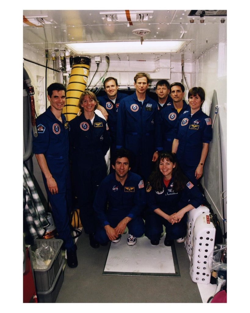 "The STS-83 crew poses in the White Room at Launch Complex 39A during the crew's <a href=""http://www-pao.ksc.nasa.gov/kscpao/release/1997/40-97.htm"">Terminal Countdown Demonstration Test (TCDT).</a> From left to right, standing, they are Payload Specialist Gregory T. Linteris, Pilot Susan L. Still, Mission Commander James D. Halsell, Mission Specialist Michael L. Gernhardt, Payload Specialist Roger K. Crouch, and Mission Specialists Donald Thomas and Janice E. Voss. Cady Coleman, the backup Mission Specialist for Donald Thomas, is kneeling on the right KSC-97pc457"