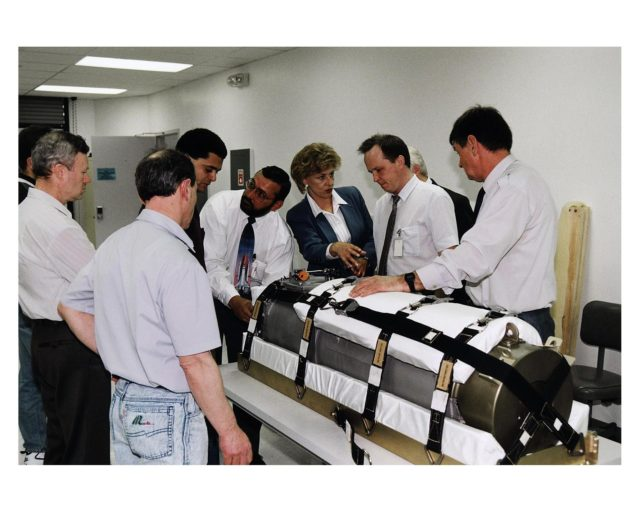 Representatives of RSC Energia in Russia and other onlookers in the SPACEHAB Payload Processing Facility examine an oxygen generator which the Space Shuttle Atlantis will carry to the Russian Mir Space Station on Mission STS-84. Sergei Romanov, second from right in the white shirt, is the spokesperson for generator manufacturer RSC Energia. The nearly 300-pound generator will be strapped down on the inside surface of a SPACEHAB Double Module for the trip to Mir. It will replace one of two Mir units that have been malfunctioning recently. The generator functions by electrolysis, which separates water into its oxygen and hydrogen components. The hydrogen is vented and the oxygen is used for breathing by the Mir crew. The generator is 4.2 feet in length and 1.4 feet in diameter. STS-84, which is planned to include a Mir crew exchange of astronaut C. Michael Foale for Jerry M. Linenger, is targeted for a May 15 liftoff. It will be the sixth Shuttle-Mir docking KSC-97pc654
