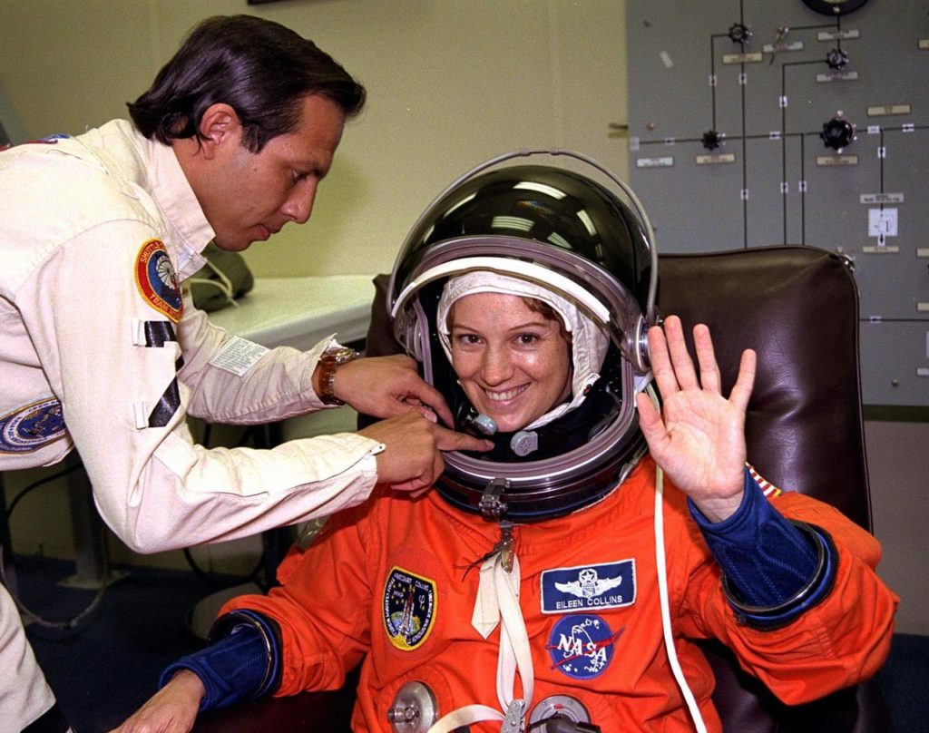 With the assistance of a suit technician, STS-84 Pilot Eileen Marie Collins finishes donning her launch and entry suit in the Operations and Checkout Building in preparation for her second Space Shuttle flight. She was the first woman Shuttle pilot on STS-63 in 1995, which was the first approach and flyaround of the Russian Space Station Mir by the Space Shuttle. Collins and six other crew members will depart shortly for Launch Pad 39A, where the Space Shuttle Atlantis awaits liftoff during an approximate 7-minute launch window which opens at about 4:08 a.m. This will be the sixth docking of the Space Shuttle with the Mir. The exact liftoff time will be determined about 90 minutes prior to launch, based on the most current location of Mir KSC-97PC793
