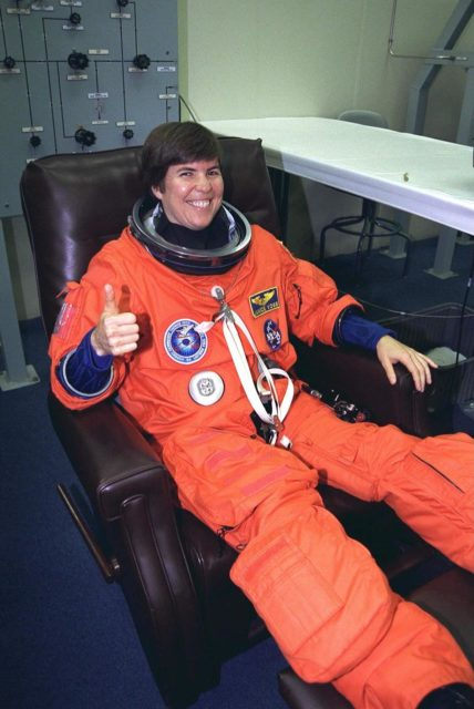STS-94 Payload Commander Janice Voss smiles  and gives a thumbs-up as she is assisted into her launch/entry suit in the Operations and  Checkout (O&C) Building. She has flown on STS-83, STS-63 and STS-57. Voss holds a  doctorate degree in aeronautics/astronautics from the Massachusetts Institute of  Technology and has earned two NASA Space Flight Medals. As Payload Commander and  a member of the Blue team, Voss will have overall responsibility for the operation of  all  of the  MSL-1  experiments. During the experimentation phase of the mission, she be  working primarily with three combustion experiments. She and six fellow crew members  will shortly depart the O&C and head for Launch Pad 39A, where the  Space Shuttle  Columbia will lift off  during a launch window that opens at 1:50 p.m. EDT,  July 1. The launch window was opened 47 minutes early to improve the opportunity to  lift off before Florida summer rain showers reached the space center KSC-97PC955