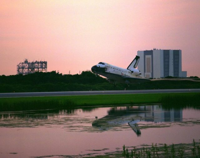 KENNEDY SPACE CENTER, FLA. -- Framed by the Vehicle Assembly Building at right and the Mate-Demate Device at left, the Space Shuttle orbiter Columbia glides onto Runway 33 at KSC's Shuttle Landing Facility at 6:46:34 a.m. EDT with Mission Commander  James D. Halsell Jr. and Pilot Susan L. Still at the controls to complete the STS-94 mission. Also on board are Mission Specialist Donald A. Thomas, Mission Specialist Michael L. Gernhardt, Payload Commander Janice Voss, and Payload Specialists Roger K. Crouch and Gregory T. Linteris. During the Microgravity Science Laboratory-1 (MSL-1) mission, the Spacelab module was used to test some of the hardware, facilities and procedures that are planned for use on the International Space Station while the flight crew conducted combustion, protein crystal growth and materials processing experiments. This mission was a reflight of  the STS-83 mission that lifted off from KSC in April of this year. That space flight was cut short due to indications of a faulty fuel cell. This was Columbia's 11th landing at KSC and the 38th landing at the space center in the history of the Shuttle program KSC-97PC1058
