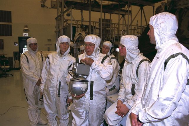 Carrying a neutron radiation detector, Fred Sanders  (at center), a health physicist with the Jet Propulsion Laboratory (JPL), and other health  physics personnel monitor radiation in the Payload Hazardous Servicing Facility after  three radioisotope thermoelectric generators (RTGs) were installed on the Cassini  spacecraft for mechanical and electrical verification tests. The RTGs will provide  electrical power to Cassini on its 6.7-year trip to the Saturnian system and during its  four-year mission at Saturn. RTGs use heat from the natural decay of plutonium to  generate electric power. The generators enable spacecraft to operate at great distances  from the Sun where solar power systems are not feasible. The Cassini mission is  targeted for an Oct. 6 launch aboard a Titan IVB/Centaur expendable launch vehicle.  Cassini is built and managed by JPL KSC-97PC1087