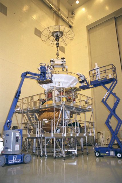 Flight mechanics from NASA's Jet Propulsion  Laboratory (JPL) in Pasadena, Calif., work on the lifting fixture that picks up the Cassini  spacecraft in KSC's Payload Hazardous Servicing Facility. The orbiter alone weighs  about 4,750 pounds (2,150 kilograms). At launch, the combined orbiter, Huygens probe,  launch vehicle adapter, and propellants will weigh about 12,346 pounds (5,600  kilograms). Scheduled for launch in October, the Cassini mission, a joint US-European  four-year orbital surveillance of Saturn's atmosphere and magnetosphere, its rings, and its  moons, seeks insight into the origins and evolution of the early solar system. JPL is  managing the Cassini project for NASA KSC-97PC1108