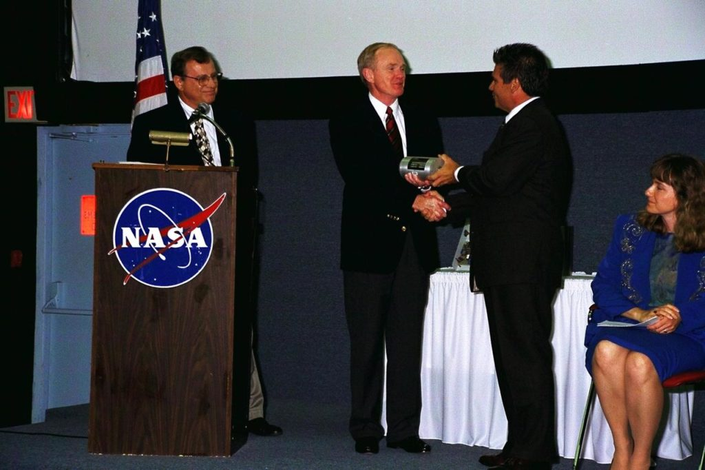 KENNEDY SPACE CENTER, FLA. -- William Saputo, L-3 Communications, presents a new piece of technology, developed through a National Aeronautics and Space Administration (NASA) partnership with industry, to Kennedy Space Center (KSC) Director Roy Bridges, Jr. (second from left). The piece of technology being presented, the Universal Signal Conditioning Amplifier (USCA), is a key component of the codeveloped Automated Data Acquisition System (ADAS) that measures temperature, pressure and vibration at KSC's launch pads. The breakthrough technology is expected to reduce sensor setup and configuration times from hours to seconds. KSC teamed up with Florida's Technological Research and Development Authority and manufacturer L-3 Communications to produce a system that would benefit the aerospace industry and other commercial markets KSC-97PC1280
