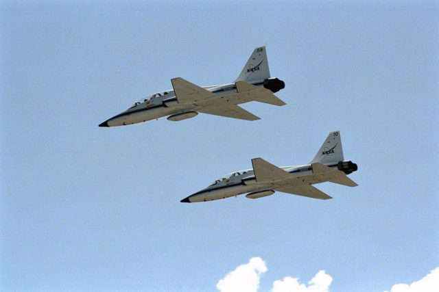 Two T-38 jets with members of the STS-86 crew fly over the space center after takeoff from KSC's Shuttle Landing Facility. The seven crew members were at KSC to participate in the Terminal Countdown Demonstration Test (TCDT), a dress rehearsal for launch. They are returning to Johnson Space Center, Houston, Texas, for final prelaunch training. STS-86 will be the seventh docking of the Space Shuttle with the Russian Space Station Mir. Liftoff aboard Atlantis is targeted for Sept. 25 from Launch Pad 39A KSC-97PC1378