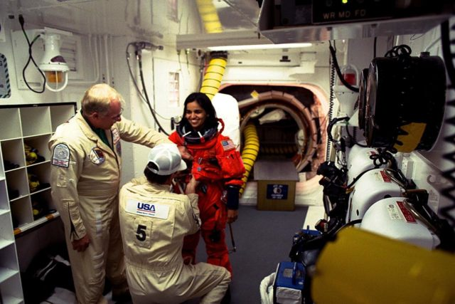 STS-87 Mission Specialist Kalpana Chawla, Ph.D., is assisted with her ascent and re-entry flight suit in the white room at Launch Pad 39B by Danny Wyatt, NASA quality assurance specialist. Kneeing before Dr. Chawla to assist her is George Schram, USA mechanical technician, as Dr. Chawla prepares to enter the Space Shuttle orbiter Columbia on launch day. STS-87 is the fourth flight of the United States Microgravity Payload and Spartan-201 KSC-97PC1702