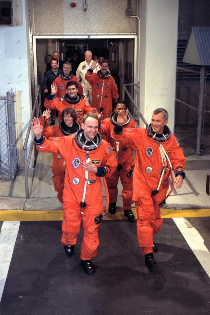 The STS-89 crew walk out of the Operations and Checkout Building and head for the Astrovan that will transport them to Launch Pad 39A, where the Space Shuttle Endeavour awaits to take them to Russia's Mir space station. Waving to the crowd and leading the way, from front to back, left to right, are Pilot Joe Edwards Jr., Commander Terrence Wilcutt, and Mission Specialists Bonnie Dunbar, Ph.D., Michael Anderson, Salizhan Sharipov of the Russian Space Agency, Andrew Thomas, Ph.D., and James Reilly, Ph.D. STS-89, slated for a 9:48 p.m. EST liftoff Jan. 22, is the eighth docking with the Russian Space Station Mir, the first Mir docking for Endeavour (all previous dockings were made by Atlantis), and the first launch of 1998. After docking with Mir, Mission Specialist Andrew Thomas, Ph.D., will transfer to the space station, succeeding David Wolf, M.D KSC-98pc213