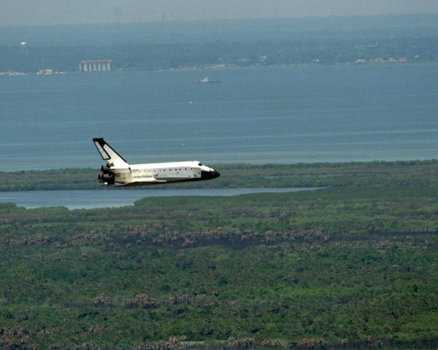 Flying along the Indian River toward KSC's Shuttle Landing Facility is the orbiter Columbia as it nears touchdown on Runway 33 to complete the nearly 16-day STS-90 mission. This unique view with Titusville and the Indian River in the background was taken from the roof of the 525-foot-high Vehicle Assembly Building. Main gear touchdown was at 12:08:59 p.m. EDT on May 3, 1998, landing on orbit 256 of the mission. The wheels stopped at 12:09:58 EDT, completing a total mission time of 15 days, 21 hours, 50 minutes and 58 seconds. The 90th Shuttle mission was Columbia's 13th landing at the space center and the 43rd KSC landing in the history of the Space Shuttle program. During the mission, the crew conducted research to contribute to a better understanding of the human nervous system. The crew of the STS-90 Neurolab mission include Commander Richard Searfoss; Pilot Scott Altman; Mission Specialists Richard Linnehan, D.V.M., Dafydd (Dave) Williams, M.D., with the Canadian Space Agency, and Kathryn (Kay) Hire; and Payload Specialists Jay Buckey, M.D., and James Pawelczyk, Ph.D KSC-98pc561