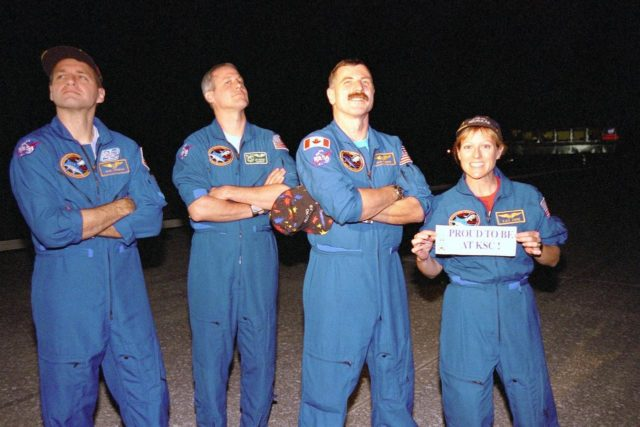 "Some of the STS-90 crew members pose at the Shuttle Landing Facility hours after arrival on May 3, ending their nearly 16-day Neurolab mission. Shown left to right are Mission Specialist Richard Linnehan, D.V.M.; Payload Specialist Jay Buckey, M.D.; and Mission Specialists Dafydd (Dave) Williams, M.D., with the Canadian Space Agency and Kathryn (Kay) Hire holding a sign that states ""Proud to be at KSC."" The 90th Shuttle mission was Columbia's 13th landing at the space center and the 43rd KSC landing in the history of the Space Shuttle program. During the mission, the crew conducted research to contribute to a better understanding of the human nervous system KSC-98pc579"