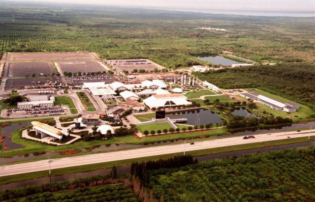 The Kennedy Space Center Visitor Center, shown in this aerial view looking south, sprawls across 70 acres on Florida's Space Coast , and is located off State Road 405, NASA Parkway, six miles inside the Space Center entrance. SR 405 can be seen at the bottom of the photo. Just above the roadway, from left can be seen the Shuttle/Gantry mockup; the Post Show Dome; the Astronaut Memorial; and to the far right, the Center for Space Education. Behind the Memorial are a cluster of buildings that include the Theater Complex, Cafeteria, Space Flight Exhibit Building, Souvenir Sales Building, Spaceport Central, and Ticket Pavilion. At the upper right are various rockets that have played a significant role in the growth of the space program. KSC-98PC-1041