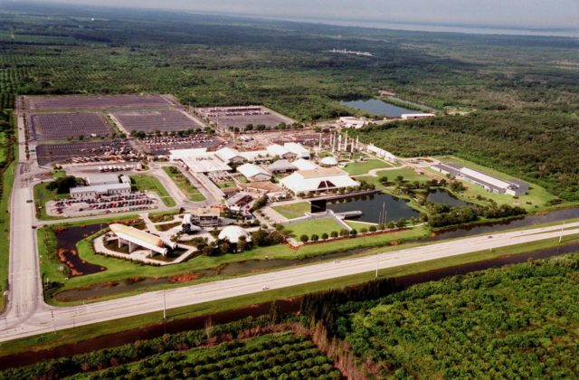 The Kennedy Space Center Visitor Complex, shown in this aerial view looking south, sprawls across 70 acres on Florida's Space Coast. It is located off State Road 405, NASA Parkway, six miles inside the Space Center entrance. SR 405 can be seen at the bottom of the photo. Just above the roadway, from left, can be seen the Shuttle/Gantry mockup, the Post Show Dome, the Astronaut Memorial, and to the far right, the Center for Space Education. Behind the Memorial are a cluster of buildings that include the Theater Complex, Cafeteria, Space Flight Exhibit Building, Souvenir Sales Building, Spaceport Central, and Ticket Pavilion. At the upper right of the site is a display of rockets that have played a significant role in the growth of the space program. Parking lots span the width of the complex on the south side. KSC-98PC-1058