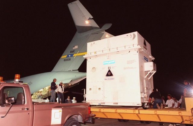 The Mars Climate Orbiter spacecraft is moved onto a flatbed for transport to the Spacecraft Assembly and Encapsulation Facility-2 (SAEF-2). It arrived at KSC's Shuttle Landing Facility aboard an Air Force C-17 cargo plane early this morning following its flight from the Lockheed Martin Astronautics plant in Denver, Colo. When it arrives at the red planet, the Mars Climate Orbiter will primarily support its companion Mars Polar Lander spacecraft, planned for launch on Jan. 3, 1999. After that, the Mars Climate Orbiter's instruments will monitor the Martian atmosphere and image the planet's surface on a daily basis for one Martian year (1.8 Earth years). It will observe the appearance and movement of atmospheric dust and water vapor, as well as characterize seasonal changes on the surface. The detailed images of the surface features will provide important clues to the planet's early climate history and give scientists more information about possible liquid water reserves beneath the surface. The scheduled launch date for the Mars Climate Orbiter is Dec. 10, 1998, on a Delta II 7425 rocket KSC-98pc1047