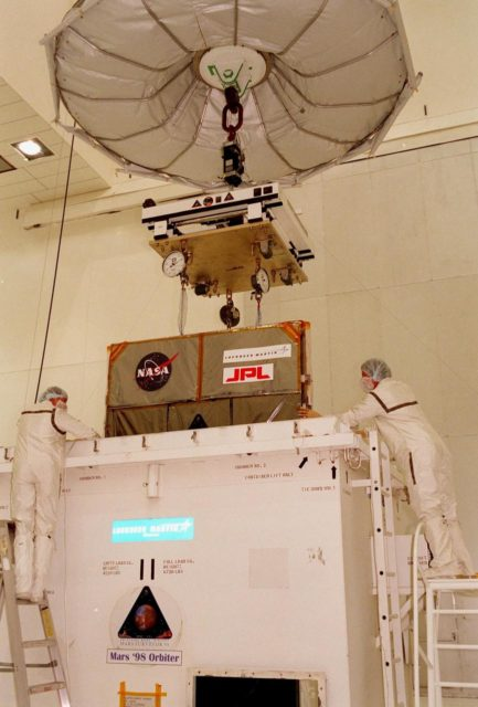 Technicians in the Spacecraft Assembly and Encapsulation Facility-2 (SAEF-2) oversee the removal of the Mars Climate Orbiter from its container. The Mars Climate Orbiter is heading for Mars where it will primarily support its companion Mars Polar Lander spacecraft, planned for launch on Jan. 3, 1999. After that, the Mars Climate Orbiter's instruments will monitor the Martian atmosphere and image the planet's surface on a daily basis for one Martian year (two Earth years). It will observe the appearance and movement of atmospheric dust and water vapor, as well as characterize seasonal changes on the surface. The detailed images of the surface features will provide important clues to the planet's early climate history and give scientists more information about possible liquid water reserves beneath the surface. The scheduled launch date for the Mars Climate Orbiter is Dec. 10, 1998, on a Boeing Delta II 7425 rocket KSC-98pc1079