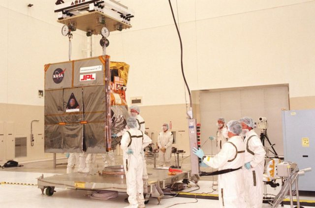 Technicians carefully maneuver the Mars Climate Orbiter toward its workstand in the Spacecraft Assembly and Encapsulation Facility-2 (SAEF-2). The Mars Climate Orbiter is heading for Mars where it will primarily support its companion Mars Polar Lander spacecraft, planned for launch on Jan. 3, 1999. After that, the Mars Climate Orbiter's instruments will monitor the Martian atmosphere and image the planet's surface on a daily basis for one Martian year (two Earth years). It will observe the appearance and movement of atmospheric dust and water vapor, as well as characterize seasonal changes on the surface. The detailed images of the surface features will provide important clues to the planet's early climate history and give scientists more information about possible liquid water reserves beneath the surface. The scheduled launch date for the Mars Climate Orbiter is Dec. 10, 1998, on a Boeing Delta II 7425 rocket KSC-98pc1082