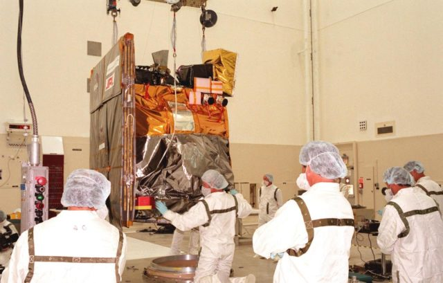 Technicians lower the Mars Climate Orbiter onto its workstand in the Spacecraft Assembly and Encapsulation Facility-2 (SAEF-2). The Mars Climate Orbiter is heading for Mars where it will primarily support its companion Mars Polar Lander spacecraft, planned for launch on Jan. 3, 1999. After that, the Mars Climate Orbiter's instruments will monitor the Martian atmosphere and image the planet's surface on a daily basis for one Martian year (two Earth years). It will observe the appearance and movement of atmospheric dust and water vapor, as well as characterize seasonal changes on the surface. The detailed images of the surface features will provide important clues to the planet's early climate history and give scientists more information about possible liquid water reserves beneath the surface. The scheduled launch date for the Mars Climate Orbiter is Dec. 10, 1998, on a Boeing Delta II 7425 rocket KSC-98pc1083