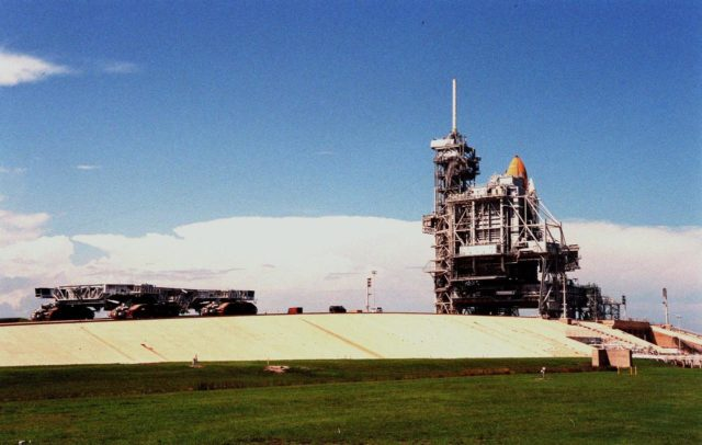(Left) The crawler transporter makes its way across Launch Pad 39-B to the Mobile Launch Platform and Space Shuttle Discovery to await possible orders for a rollback. KSC managers developed a precautionary plan to roll back Discovery to the Vehicle Assembly Building in the event that Hurricane Georges threatens Central Florida. The decision was made to minimize risk and provide protection to the Space Shuttle national asset KSC-98pc1127