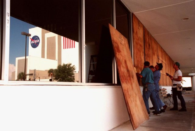 Workers put up plywood barriers on the windows of the Operations Support Building (OSB) as part of a precautionary plan in the event that Hurricane Georges threatens Central Florida. In light of the unpredictable nature of hurricanes, the decision was made to minimize risk and provide protection to KSC personnel and to the Space Shuttle national asset. The Vehicle Assembly Building is reflected (left) in the uncovered windows of the OSB KSC-98pc1129