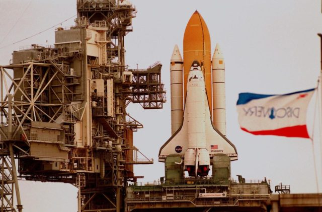 In this close-up, Space Shuttle Discovery sits atop the Mobile Launch Platform on Launch Pad 39-B, with the Rotating Service Structure moved back, to await rollback decision. The flag at right shows the increased wind blowing out of the south. KSC managers developed a precautionary plan to roll back Discovery to the Vehicle Assembly Building in the event that Hurricane Georges threatens Central Florida. The decision was made in order to minimize risk and provide protection to the Space Shuttle, a national asset KSC-98pc1147