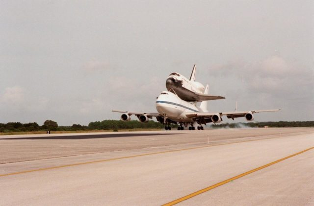 KENNEDY SPACE CENTER, FLA. -- The Shuttle Carrier Aircraft with orbiter Atlantis on top touches down at the Shuttle Landing Facility. Atlantis returns home after a 10-month stay in the Palmdale, CA, orbiter processing facility undergoing extensive inspections and modifications. They included several upgrades enabling it to support International Space Station missions, such as adding an external airlock for ISS docking missions and installing thinner, lighter thermal protection blankets for weight reduction which will allow it to haul heavier cargo. The flight from Palmdale included a fueling stop in Ft. Hood, TX, and overnight stay at Ft. Campbell, KY. Atlantis will undergo preparations in the Orbiter Processing Facility at KSC for its planned flight in June 1999 KSC-98pc1160