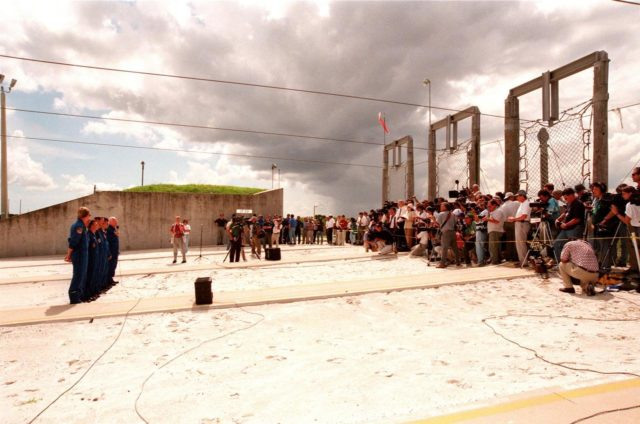 In front of the bunker near Launch Pad 39-B, the STS-95 crew members (at left) respond to questions about the mission and training from 106 reporters and photographers during a brief break from the Terminal Countdown Demonstration Test (TCDT). From left they are Mission Specialist Scott E. Parazynski, Mission Specialist Stephen K. Robinson, who also serves as Payload Commander, Pilot Steven W. Lindsey, Mission Commander Curtis L. Brown, Mission Specialist Pedro Duque of Spain, representing the European Space Agency (ESA), Payload Specialist Chiaki Mukai, representing the National Space Development Agency of Japan (NASDA), and Payload Specialist John H. Glenn Jr., senator from Ohio, holding a microphone. The crew were at the pad for emergency egress training after the break. Above them are the slidewires leading to the catch nets for the baskets that are used in emergency egress. The TCDT also involves mission familiarization activities and a simulated main engine cut-off exercise. The STS-95 mission, targeted for liftoff on Oct. 29, includes research payloads such as the Spartan solar-observing deployable spacecraft, the Hubble Space Telescope Orbital Systems Test Platform, the International Extreme Ultraviolet Hitchhiker, as well as the SPACEHAB single module with experiments on space flight and the aging process. Following the TCDT, the crew will be returning to Houston for final flight preparations KSC-98pc1267