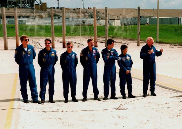 Near Launch Pad 39-B, the STS-95 crew members respond to questions about the mission and training from reporters during a brief break from the Terminal Countdown Demonstration Test (TCDT). From left they are Mission Specialist Scott E. Parazynski, Mission Specialist Stephen K. Robinson, who also serves as Payload Commander, Pilot Steven W. Lindsey, Mission Commander Curtis L. Brown, Mission Specialist Pedro Duque of Spain, representing the European Space Agency (ESA), Payload Specialist Chiaki Mukai, representing the National Space Development Agency of Japan (NASDA), and Payload Specialist John H. Glenn Jr., senator from Ohio, holding a microphone. The crew were at the pad for emergency egress training after the break. Behind them are the catch nets for the slidewire baskets that are used in emergency egress. The TCDT also involves mission familiarization activities and a simulated main engine cut-off exercise. The STS-95 mission, targeted for liftoff on Oct. 29, includes research payloads such as the Spartan solar-observing deployable spacecraft, the Hubble Space Telescope Orbital Systems Test Platform, the International Extreme Ultraviolet Hitchhiker, as well as the SPACEHAB single module with experiments on space flight and the aging process. Following the TCDT, the crew will be returning to Houston for final flight preparations KSC-98pc1268