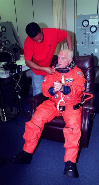 In the Operations and Checkout Building, suit technician George Brittingham helps STS-95 Payload Specialist John H. Glenn Jr., senator from Ohio, with his suit. The STS-95 crew were conducting flight crew equipment fit checks prior to launch on Oct. 29. STS-95 is expected to launch at 2 p.m. EST on Oct. 29, last 8 days, 21 hours and 49 minutes, and land at 11:49 a.m. EST on Nov. 7 KSC-98pc1416