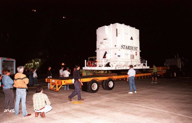 At the Shuttle Landing Facility, workers observe the loading of the crated Stardust spacecraft onto a trailer for transporting to the Payload Hazardous Service Facility. Built by Lockheed Martin Astronautics near Denver, Colo., for the Jet Propulsion Laboratory (JPL) and NASA, the spacecraft Stardust will use a unique medium called aerogel to capture comet particles flying off the nucleus of comet Wild 2 in January 20004, plus collect interstellar dust for later analysis. Stardust will be launched aboard a Boeing Delta 7426 rocket from Complex 17, Cape Canaveral Air Station, targeted for Feb. 6, 1999. The collected samples will return to Earth in a re-entry capsule to be jettisoned from Stardust as it swings by in January 2006 KSC-98pc1623