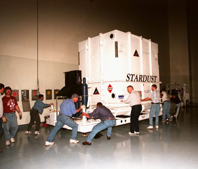 In the Payload Hazardous Service Facility, workers oversee the arrival of the crated Stardust spacecraft. Built by Lockheed Martin Astronautics near Denver, Colo., for the Jet Propulsion Laboratory (JPL) and NASA, the spacecraft Stardust will use a unique medium called aerogel to capture comet particles flying off the nucleus of comet Wild 2 in January 2004, plus collect interstellar dust for later analysis. Stardust will be launched aboard a Boeing Delta 7426 rocket from Complex 17, Cape Canaveral Air Station, targeted for Feb. 6, 1999. The collected samples will return to Earth in a re-entry capsule to be jettisoned from Stardust as it swings by in January 2006 KSC-98pc1624