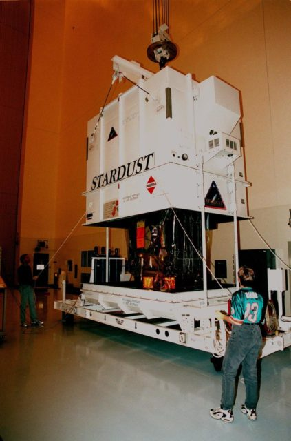 In the Payload Hazardous Service Facility, workers lift the cover that protected the Stardust spacecraft during its journey. Built by Lockheed Martin Astronautics near Denver, Colo., for the Jet Propulsion Laboratory (JPL) and NASA, the spacecraft Stardust will use a unique medium called aerogel to capture comet particles flying off the nucleus of comet Wild 2 in January 2004, plus collect interstellar dust for later analysis. Stardust will be launched aboard a Boeing Delta 7426 rocket from Complex 17, Cape Canaveral Air Station, targeted for Feb. 6, 1999. The collected samples will return to Earth in a re-entry capsule to be jettisoned from Stardust as it swings by in January 2006 KSC-98pc1630