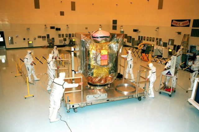 In the Payload Hazardous Service Facility, workers move the Stardust spacecraft on its workstand from the air lock to the high bay. The spacecraft will undergo installation and testing of the solar arrays, plus final installation and testing of spacecraft instruments followed by an overall spacecraft functional test. Built by Lockheed Martin Astronautics near Denver, Colo., for the Jet Propulsion Laboratory (JPL) and NASA, the spacecraft Stardust will use a unique medium called aerogel to capture comet particles flying off the nucleus of comet Wild 2 in January 2004, plus collect interstellar dust for later analysis. Stardust will be launched aboard a Boeing Delta 7426 rocket from Complex 17, Cape Canaveral Air Station, targeted for Feb. 6, 1999. The collected samples will return to Earth in a re-entry capsule to be jettisoned from Stardust as it swings by Earth in January 2006 KSC-98pc1634