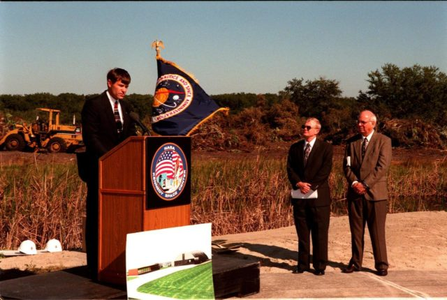 Donald McMonagle (left), manager, Launch Integration, speaks to federal and state elected officials during the ground breaking ceremony for a multi-purpose hangar, phase one of the Reusable Launch Vehicle (RLV) Support Complex to be built near the Shuttle Landing Facility. At right are Center Director Roy Bridges and Executive Director of the Spaceport Florida Authority (SFA) Ed O'Connor. The new complex is jointly funded by SFA, NASA's Space Shuttle Program and Kennedy Space Center. It is intended to support the Space Shuttle and other RLV land X-vehicle systems. Completion is expected by the year 2000 KSC-98pc1881