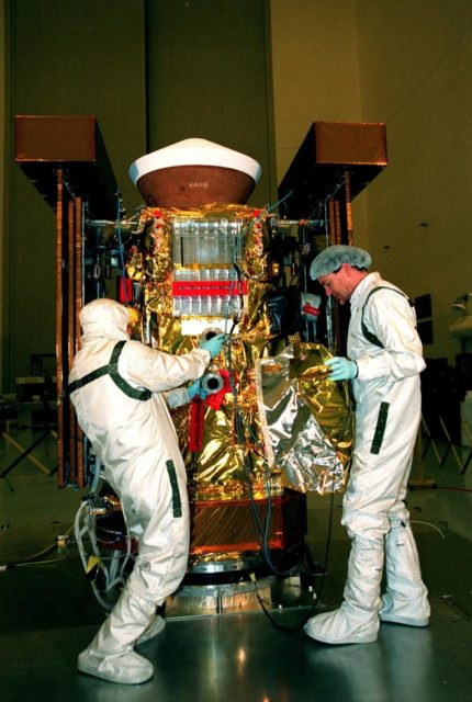 """In the Payload Hazardous Servicing Facility, Randy Scott (left) and Pat Wedeman (right) , with Lockheed Martin Astronautics, insulate the <a href=""""http://www-pao.ksc.nasa.gov/kscpao/captions/subjects/stardust.htm"""">Stardust</a> spacecraft. Stardust will use a unique medium called aerogel to capture comet particles flying off the nucleus of comet Wild 2 in January 2004, plus collect interstellar dust for later analysis. The collected samples will return to Earth in the SRC to be jettisoned as it swings by Earth in January 2006. Stardust is scheduled to be launched aboard a Boeing Delta 7426 rocket from Complex 17, Cape Canaveral Air Station, on Feb. 6, 1999 KSC-98pc1893"""