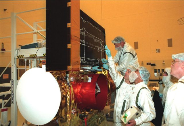 """Workers in the Payload Hazardous Servicing Facility check solar panels on the <a href=""""http://www-pao.ksc.nasa.gov/kscpao/captions/subjects/stardust.htm""""> Stardust</a> spacecraft before performing lighting tests. Stardust is scheduled to be launched aboard a Boeing Delta II rocket from Launch Pad 17A, Cape Canaveral Air Station, on Feb. 6, 1999, for a rendezvous with the comet Wild 2 in January 2004. Stardust will use a substance called aerogel to capture comet particles flying off the nucleus of the comet, plus collect interstellar dust for later analysis. The collected samples will return to Earth in a sample return capsule (its white cap is seen on the left) to be jettisoned as it swings by Earth in January 2006 KSC-99pc37"""