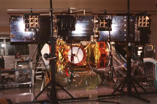 """In the Payload Hazardous Servicing Facility, a worker (left) conducts lighting tests on the fully extended solar panels of the <a href=""""http://www-pao.ksc.nasa.gov/kscpao/captions/subjects/stardust.htm""""> Stardust</a>spacecraft. Stardust is scheduled to be launched aboard a Boeing Delta II rocket from Launch Pad 17A, Cape Canaveral Air Station, on Feb. 6, 1999, for a rendezvous with the comet Wild 2 in January 2004. Stardust will use a substance called aerogel to capture comet particles flying off the nucleus of the comet, plus collect interstellar dust for later analysis. The collected samples will return to Earth in a sample return capsule to be jettisoned as it swings by Earth in January 2006 KSC-99pc41"""